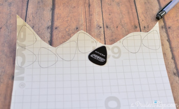 Trace guitar pick on vinyl to make petals