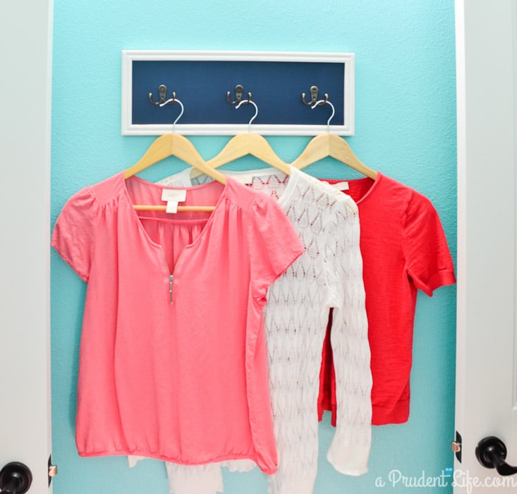 Extra hooks in a laundry room help keep everything organized. Click to see the rest of this bright & happy room!