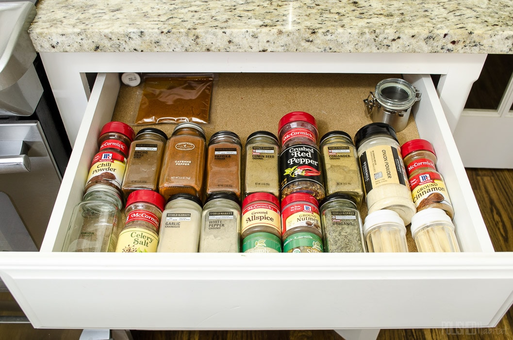 Use a drawer to store spices. Click for more cabinet organizing ideas from Polished Habitat.