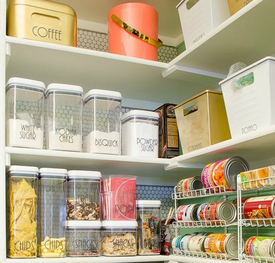 Organized pantry with clear food storage containers and can racks