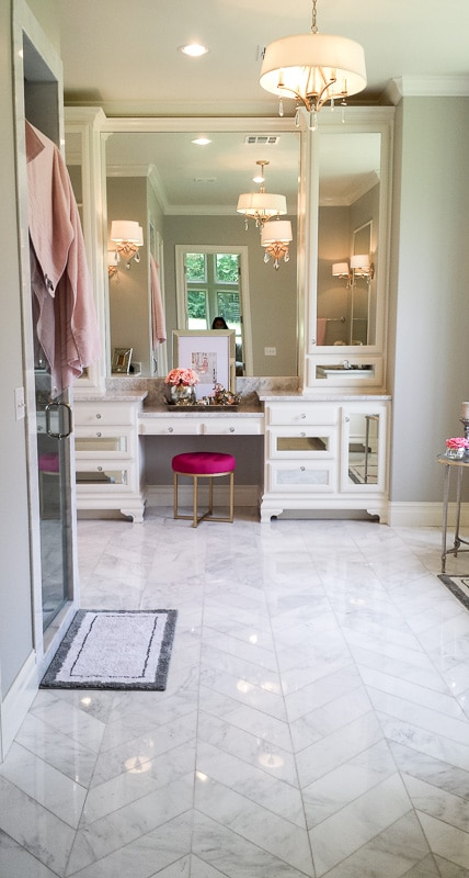 This is my dream bathroom - herringbone marble, pink accents, mirrored vanity. It's all gorgeous.