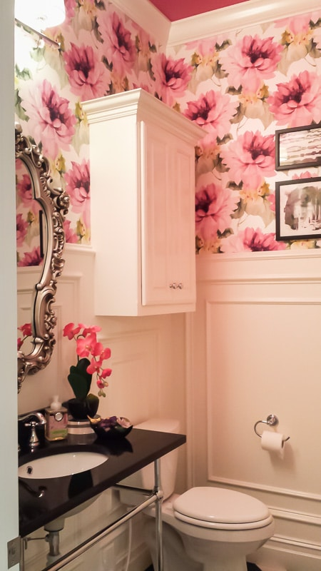 This bold powder room design is a mix of traditional and modern with classic molding and a surprising pop of color.