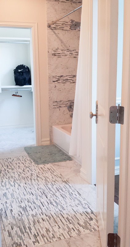 Smaller accent tiles makes this marble bathroom fun for kids.