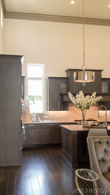 Silver drum pendants add some shine against the gray kitchen cabinets.