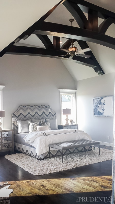 Gorgeous wood beams top this modern master bedroom