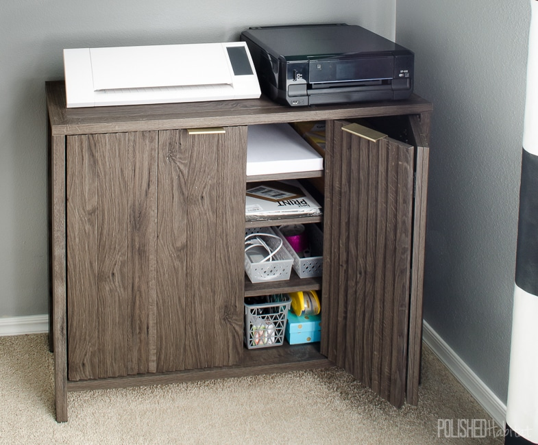Using closed storage under the printer allows quick, but hidden, access to printer paper and extra ink cartridges. Click to see the full shared home office tour!