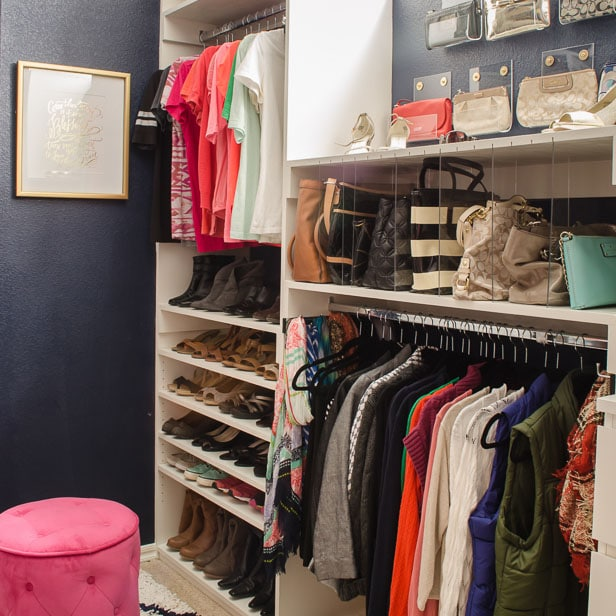 Navy walk-in closet with white shelves and purse storage