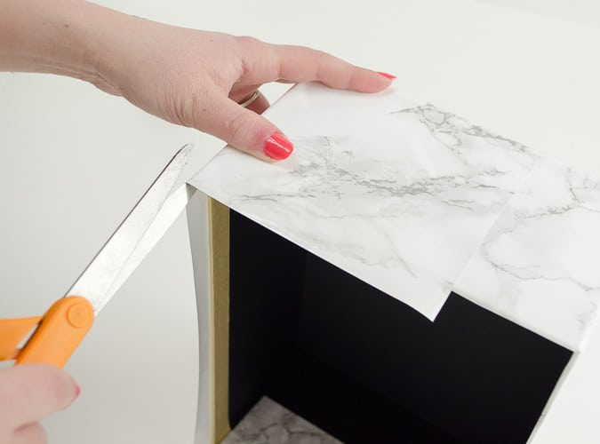 Marble contact paper plus an inexpensive photo box can be combined into inexpensive chic storage. Love the tips on how to make the corners look good!