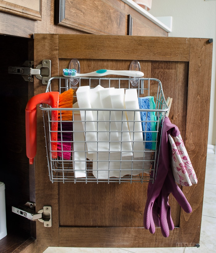 Love this idea for the bathroom! Use a basket to hold cleaning tools on the cabinet door.