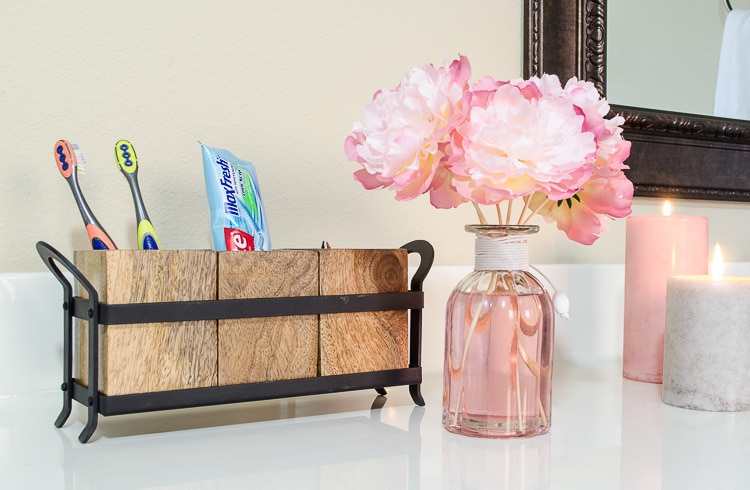Think outside the box for bathroom storage - this cute toothbrush holder is actually a utensil holder from Pier 1.