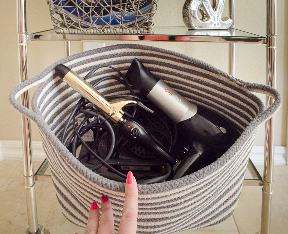 LOVE THIS! Get a basket for the blow dryer and straighter to hide the mess of cords out of sight in the bathroom. Click for more bathroom organizing ideas!