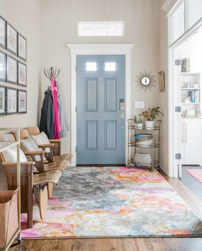 Entryway with gray door, bold rug, and vintage auditorium seating.