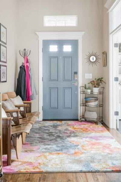 Entry way with gray door, pink rug, and vintage auditorium seats.