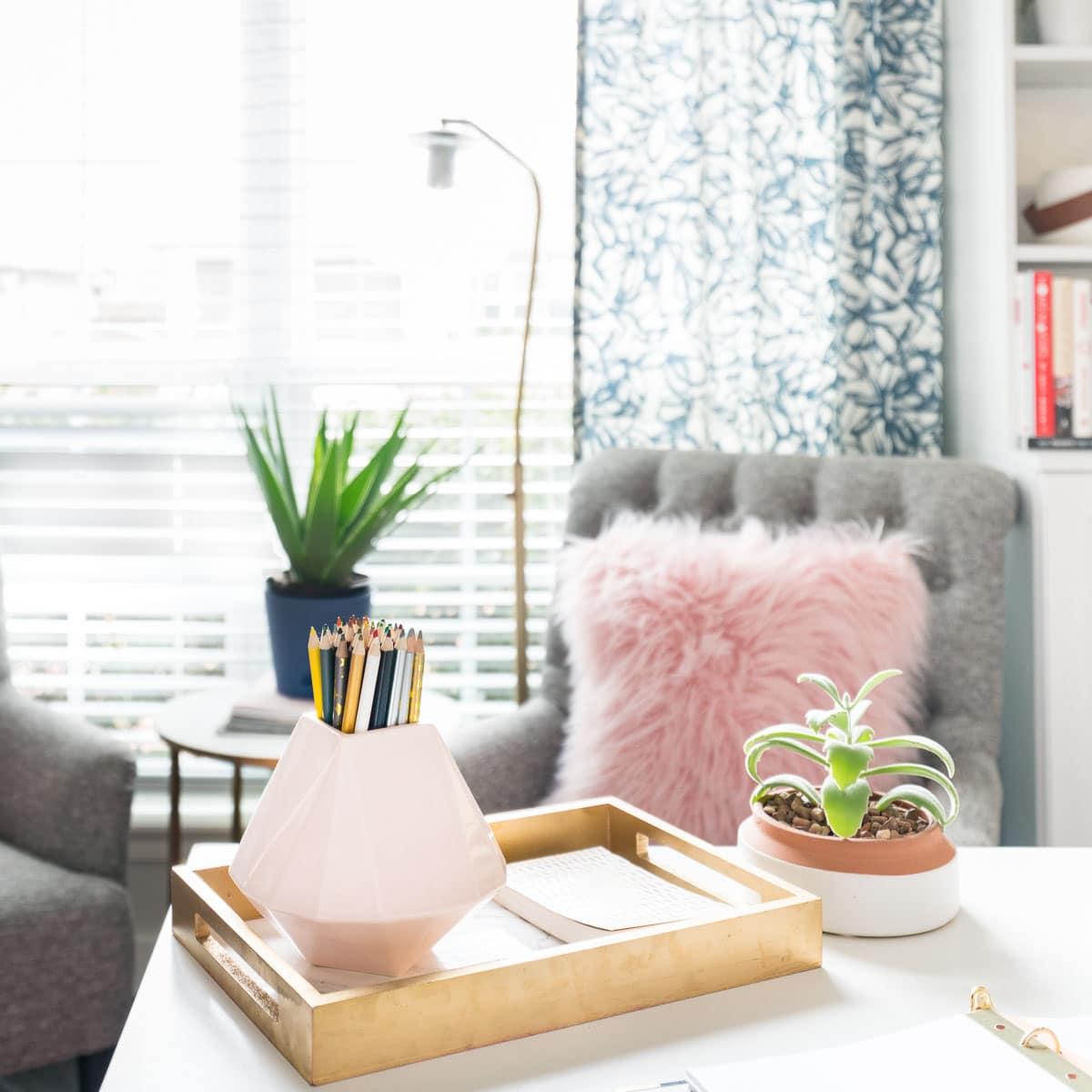 Small pink vase on white desk in feminine office.