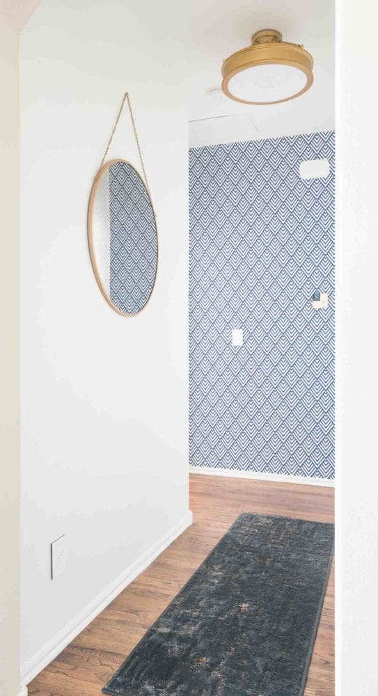 Round mirror on white walls in short hallway