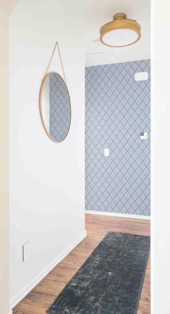 Round mirror on white walls in short hallway