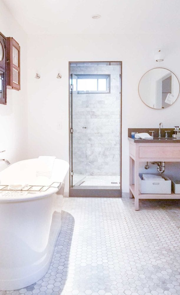 White Bathroom with freestanding tub, marble floors, and marble shower Vagabond House Inn