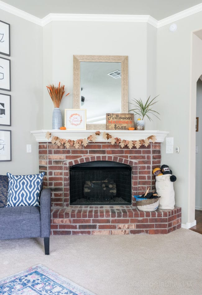 Brick fireplace with white mantel decorated for fall.