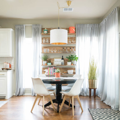Dining nook with white modern chairs and IKEA Skogsta wood wall shelve