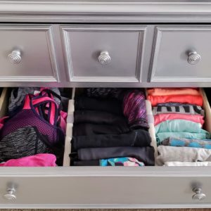 Sports bras, yoga pants, and tank tops organized in a drawer