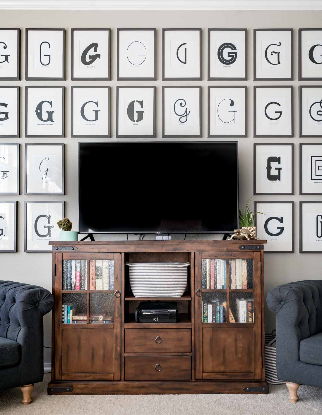 TV on wood console surrounded by typography G art