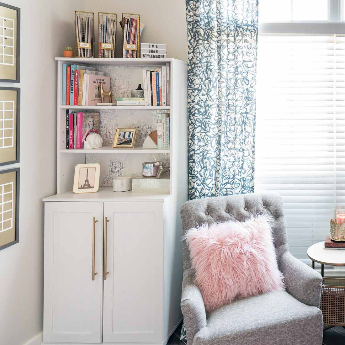 White bookcase in feminie office with gray chair and pink pillow