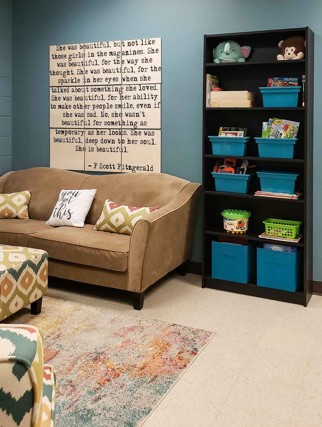 Teal wall and a bookcase full of toys for the kids.