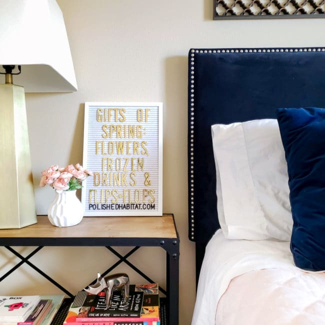 Navy headboard and nightstand with white letterboard and gold lamp