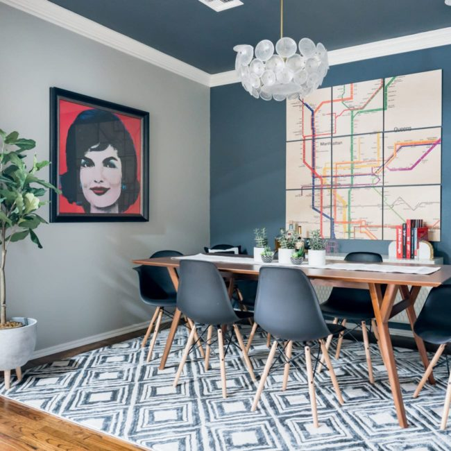 Dining room with black and white geometric rug and large Jackie O Warhol print