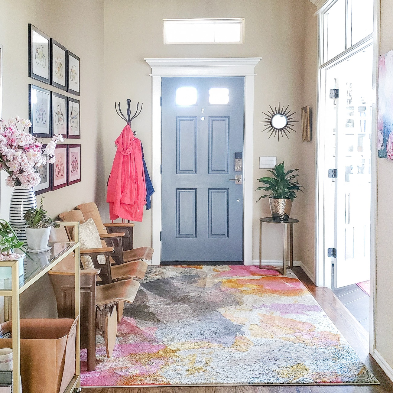 Entryway with bold pink rugh and gray front door.