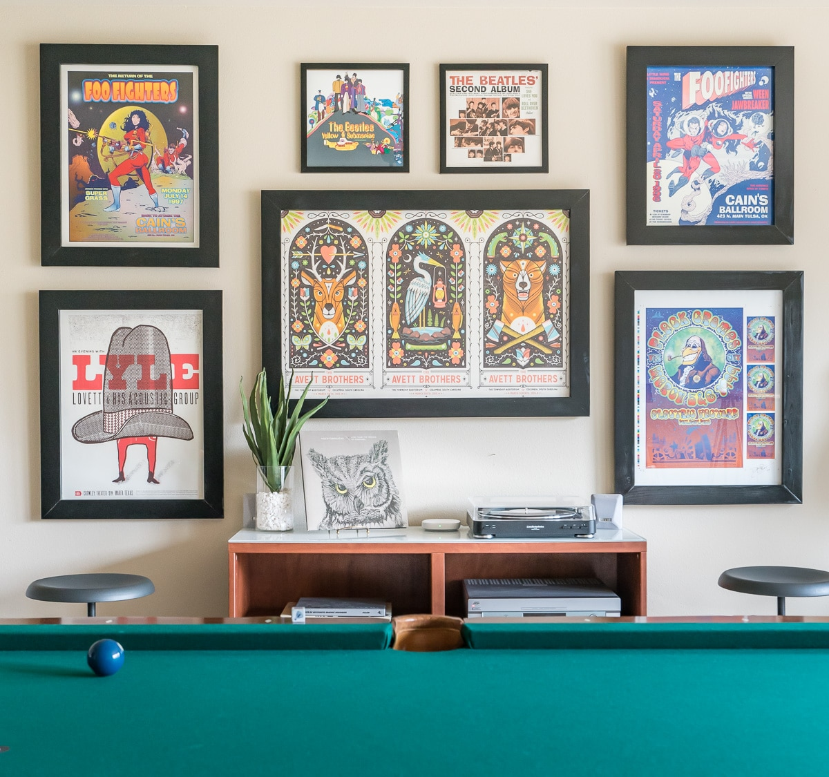 Colorful concert poster gallery wall in in game room with record player and pool table