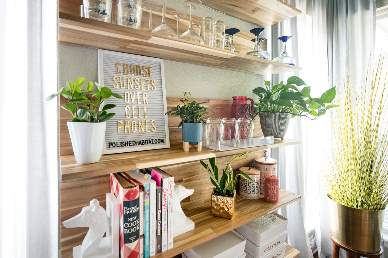 Wood shelves with white letter board saying - Choose Sunsets Over Cell Phones
