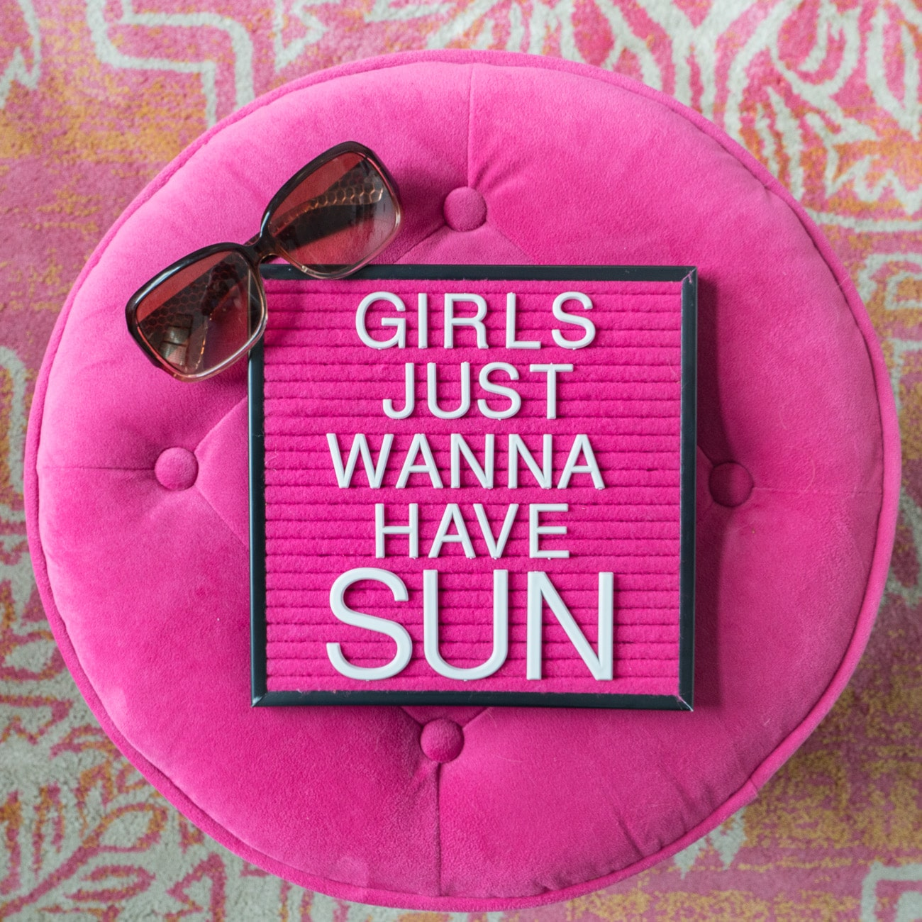 """Pink round ottoman with pink letterboard saying """"Girls Just Wanna Have Sun"""""""