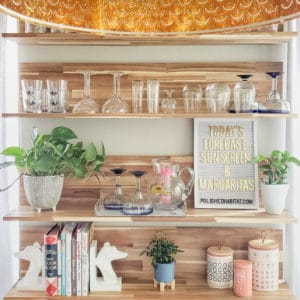 """Wood kitchen shelves with glassware and white letter board with gold letters saying """"Today's Forecast: Sunshine & Margaritas"""""""