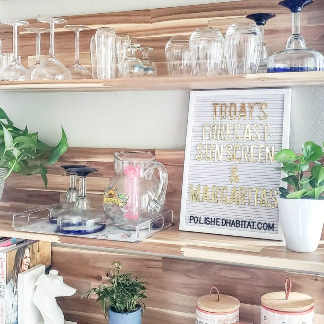 "Wood kitchen shelves with glassware and white letter board with gold letters saying ""Today's Forecast: Sunshine & Margaritas"""