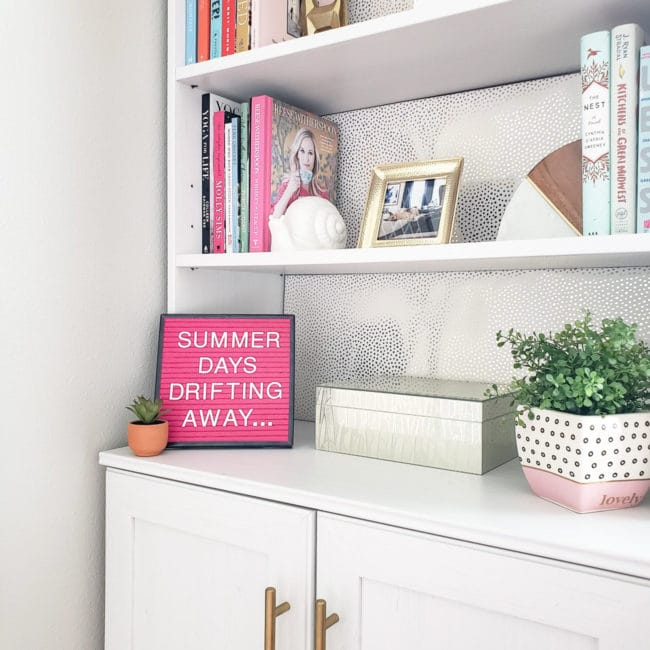 Close up of White bookcase with pink letterboard that says Summer Days Drifting Away