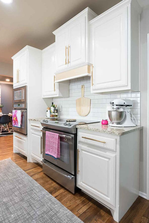 White kitchen with gold hardware and pink accents