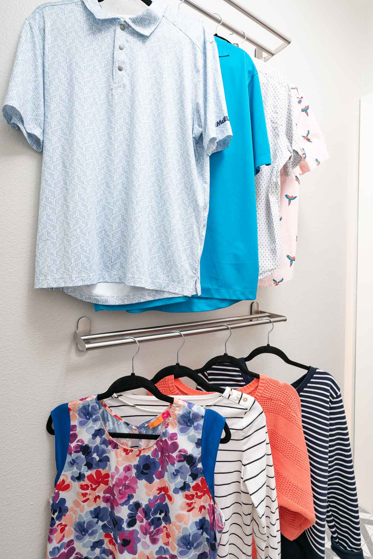 mens clothes hanging on rod above women's clothing on lower rod