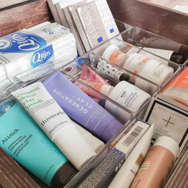 Bathroom products stored in clear organizers inside a drawer