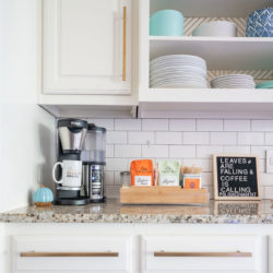 Cofffee station on kitchen counter - white cabinets with gold pulls