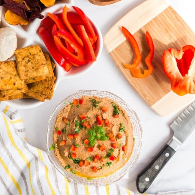 mediterranean hummus in bowl with red pepper and crackers