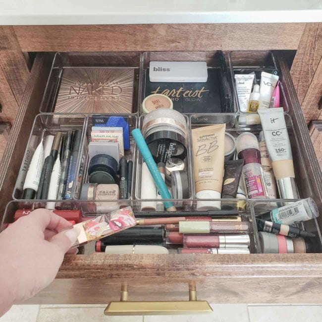 Hand putting makeup into organized drawer
