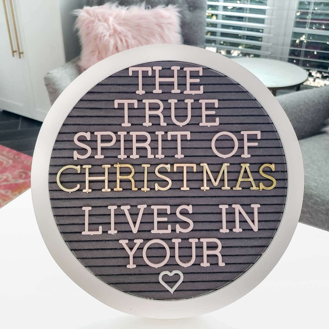 Round letter board with gray felt and white frame.
