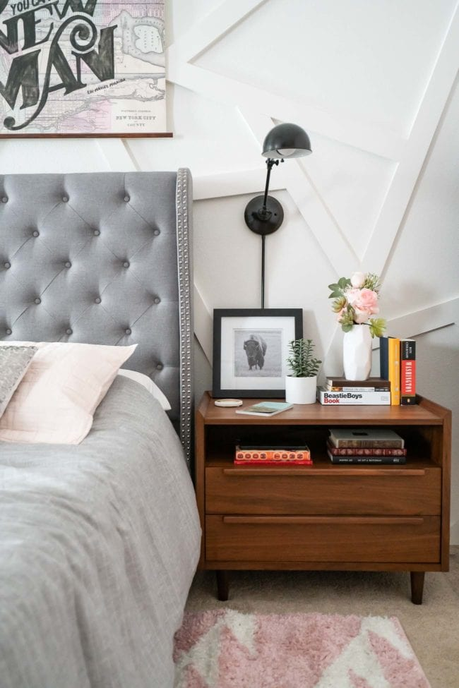 tall gray tufted headboard with wood nightstand