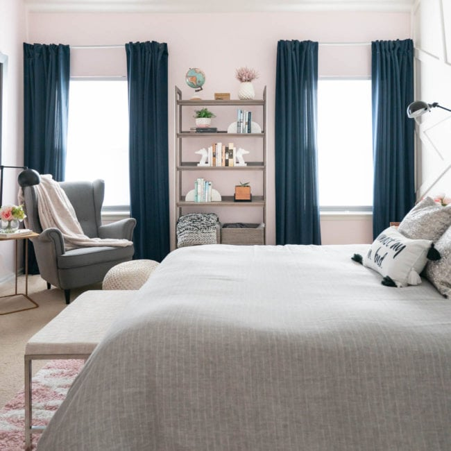bedroom with two windows - navy drapes and gray bedding with pink walls