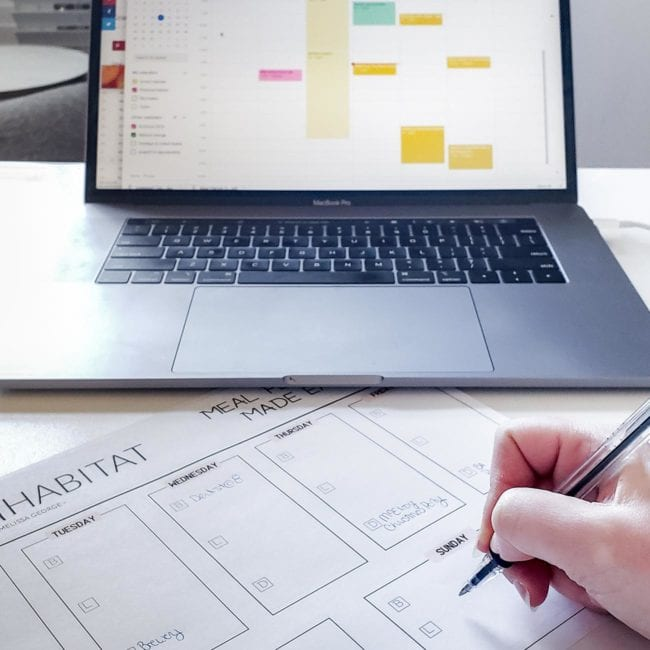 Meal plan printable on desk in front of laptop open to calendar