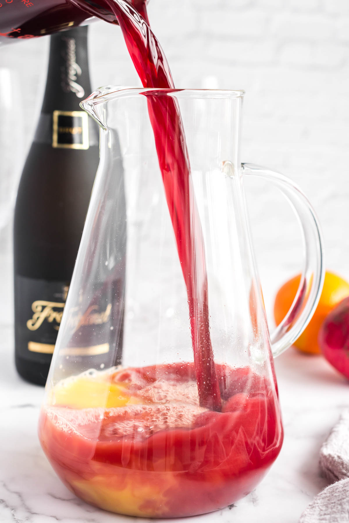 Pomegranate juice poured into a clear pitcher of orange juice for mimosa