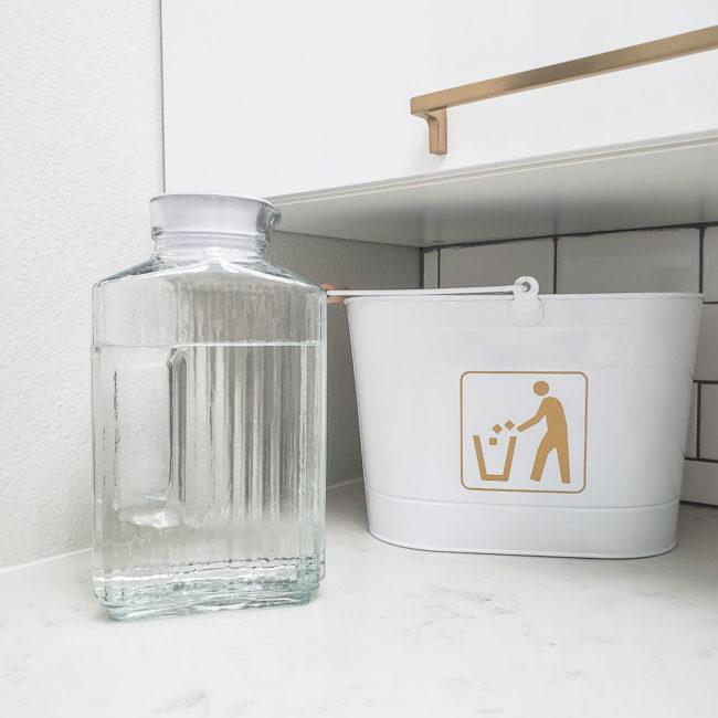 Glass jar of vinegar in white laundry room