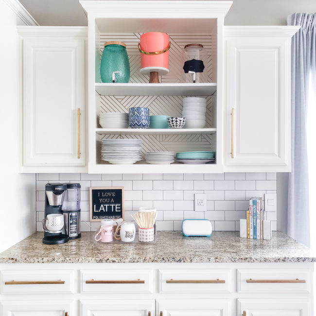 White kitchen cabinets with granite countertop featuring a coffee station, Cricut Joy & cookbooks.