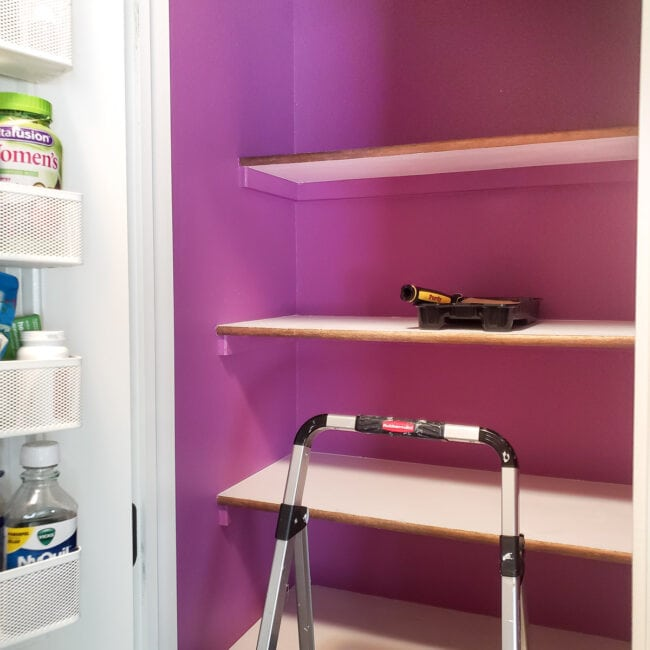 Empty white shelves in purple closet